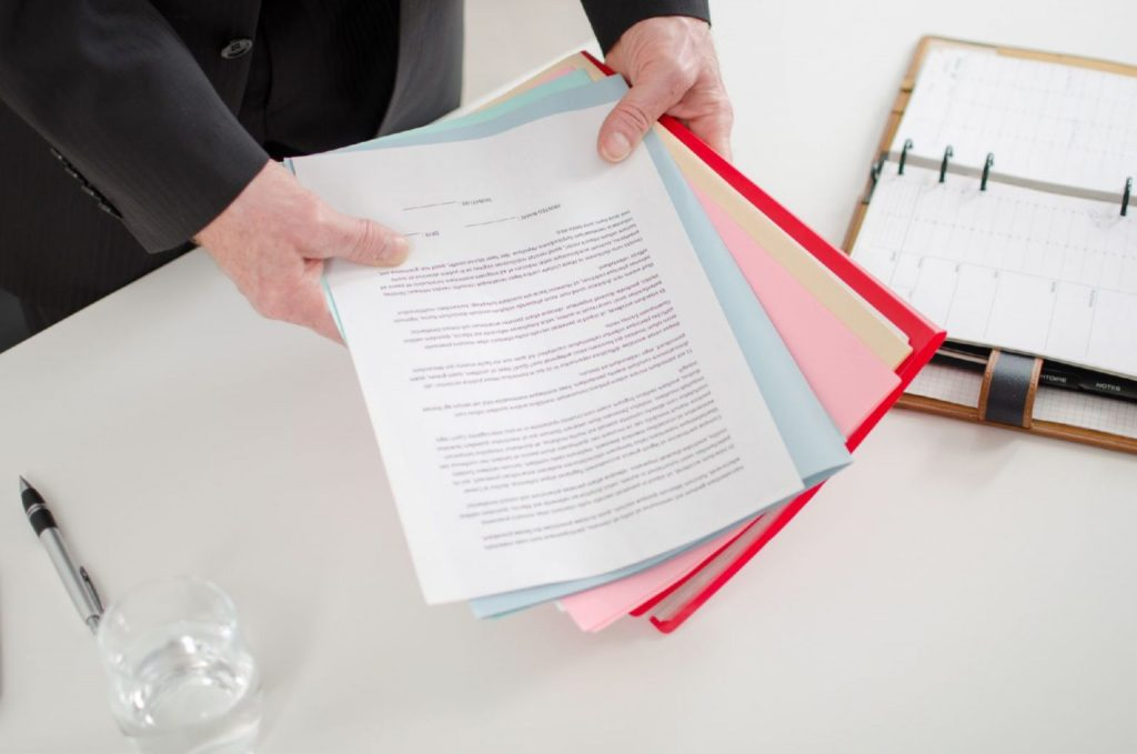 Businessman holding documents on his desk